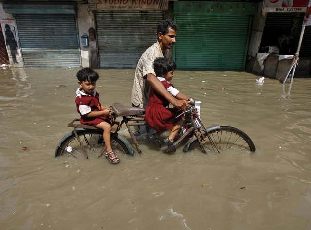 A man transports his daughters from their school on a bicycle through a flooded road after heavy monsoon rains in the eastern India caused the rise in water levels of river Ganga and its tributaries in Kolkata, India, August 3, 2015. At least 75 people have died and tens of thousands have had to take refuge in state-run relief camps after heavy rains caused floods and landslides in eastern India, government officials and aid groups said on Monday. (Photo by Rupak De Chowdhuri/Reuters)