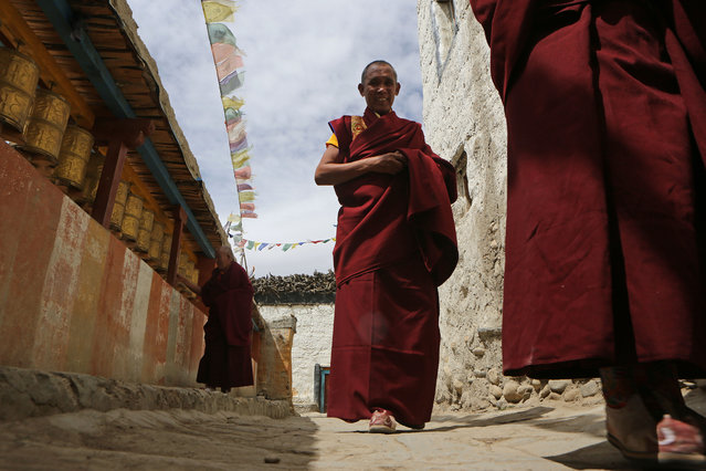 Monks walk from the Choede Monastery to the city's main square to perform during the Tenchi Festival on May 27, 2014 in Lo Manthang, Nepal. The Tenchi Festival takes place annually in Lo Manthang, the capital of Upper Mustang and the former Tibetan Kingdom of Lo. Each spring, monks perform ceremonies, rites, and dances during the Tenchi Festival to dispel evils and demons from the former kingdom. (Photo by Taylor Weidman/Getty Images)