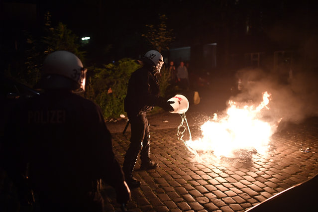 "Police forces put out a small fire after protestors erected burning barricades in front of the Rote Flora left-wing centre during a march on July 7, 2017 in Hamburg, Germany. Leaders of the G20 group of nations are arriving in Hamburg today for the July 7-8 economic summit and authorities are bracing for large-scale and disruptive protest efforts. As heavy protests are expected tonight at the ""Welcome to Hell"" anti-G20 protest. (Photo by Alexander Koerner/Getty Images)"