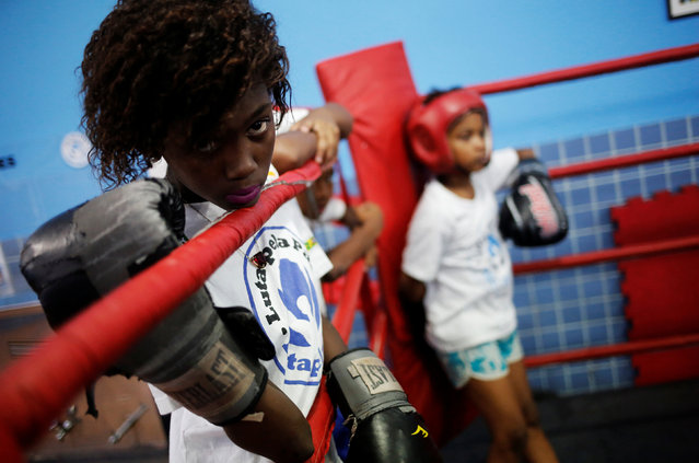 A girl looks at other children practicing on a boxing ring during an exercise session at a boxing school, in the Mare favela of Rio de Janeiro, Brazil, June 2, 2016. (Photo by Nacho Doce/Reuters)