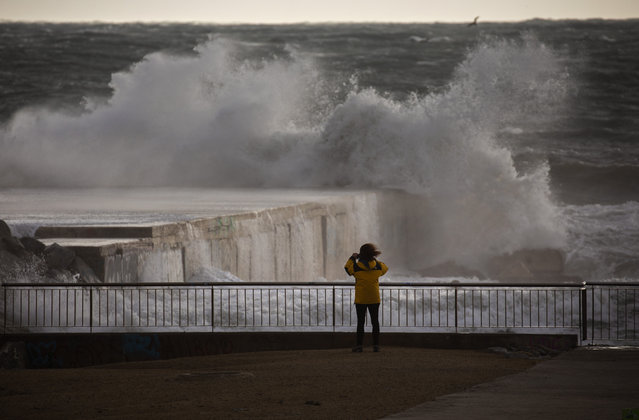 A woman photographs the Mediterranean sea during strong winds in Barcelona, Spain, Monday, January 20, 2020. Two people have died as storms carrying heavy snowfalls and gale-force winds lashed many parts of Spain on Monday. The storm has forced the closure of Alicante airport and some 30 roads in eastern region. Six provinces are on top alert. (Photo by Emilio Morenatti/AP Photo)