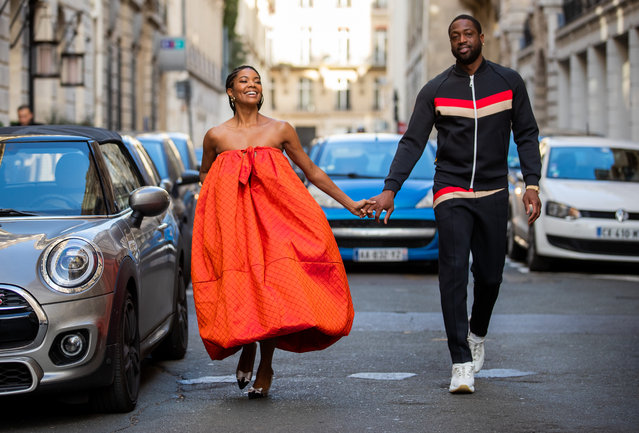 Couple Gabrielle Union is seen wearing orange off shoulder dress Christopher John Rogers and heels and Dwyane Wade wearing black track suit with red and beige stripes during Paris Fashion Week – Menswear F/W 2020-2021 on January 19, 2020 in Paris, France. (Photo by Christian Vierig/Getty Images)