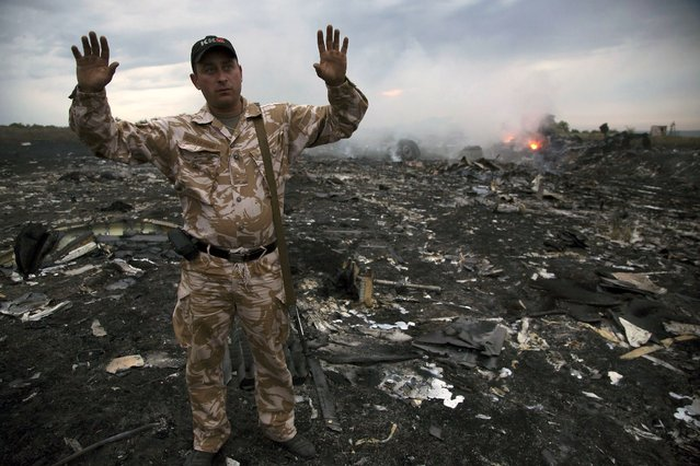 A man gestures at a crash site of a passenger plane near the village of Grabovo, Ukraine, Thursday, July 17, 2014. Ukraine said a passenger plane carrying 295 people was shot down Thursday as it flew over the country, and both the government and the pro-Russia separatists fighting in the region denied any responsibility for downing the plane. (Photo by Dmitry Lovetsky/AP Photo)