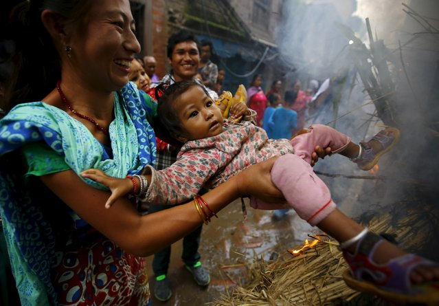 A woman swings a child around a fire, where an effigy of the demon Ghantakarna was burnt to symbolize the destruction of evil, during the Ghantakarna festival at the ancient city of Bhaktapur, Nepal August 12, 2015. (Photo by Navesh Chitrakar/Reuters)