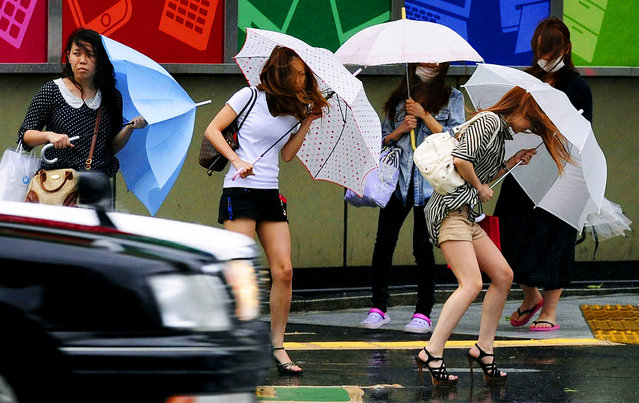 Women walk in the strong winds from Typhoon Guchol in Nagoya, Japan on June 19, 2012