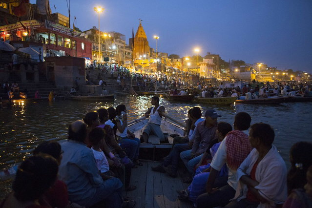 Hindu devotees travel past holy ghats on the banks of the river Ganges in Varanasi, in the northern Indian state of Uttar Pradesh, June 16, 2014. (Photo by Danish Siddiqui/Reuters)