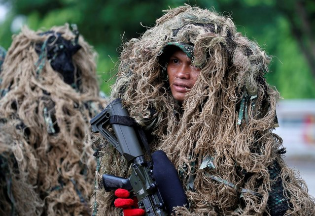 Soldiers wear sniper attire as they take part in a military parade to honor Philippine President Benigno Aquino, a few days before he leaves office for incoming President-elect Rodrigo Duterte at military's main Camp Aguinaldo in Quezon city, Metro Manila, Philippines June 27, 2016. (Photo by Erik De Castro/Reuters)