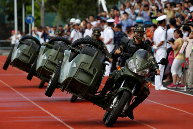 People's Liberation Army soldiers perform driving stunts at a naval base, celebrating the 19th anniversary of Hong Kong's handover to Chinese sovereignty from British rule, in Hong Kong July 1, 2016. (Photo by Bobby Yip/Reuters)