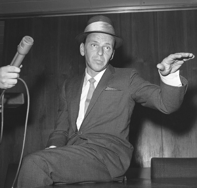 """Singer Frank Sinatra talks with newsmen at New York's Idlewild airport, June 17, 1962, after returning from a series of benefit concerts around the world. Sinatra said his 20-month singing tour raised about $1,200,000 for handicapped and crippled children. The singer called his visits to eight nations and the British crown colony of Hong Kong """"most gratifying"""". (Photo by Jacob Harris/AP Photo)"""