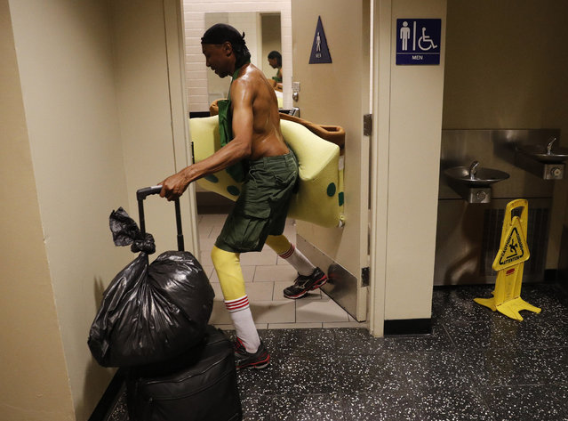 In this Monday, April 17, 2017 photo, covered in sweat, impersonator Belnarr Golden enters a public restroom with his SpongeBob SquarePants costume folded in half after working on Hollywood Boulevard in Los Angeles. (Photo by Jae C. Hong/AP Photo)