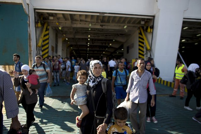 """A Syrian refugee woman carries a child as they walk out of """"Eleftherios Venizelos"""" passenger ship after its arrival at the port of Piraeus near Athens, Greece, August 20, 2015. (Photo by Stoyan Nenov/Reuters)"""