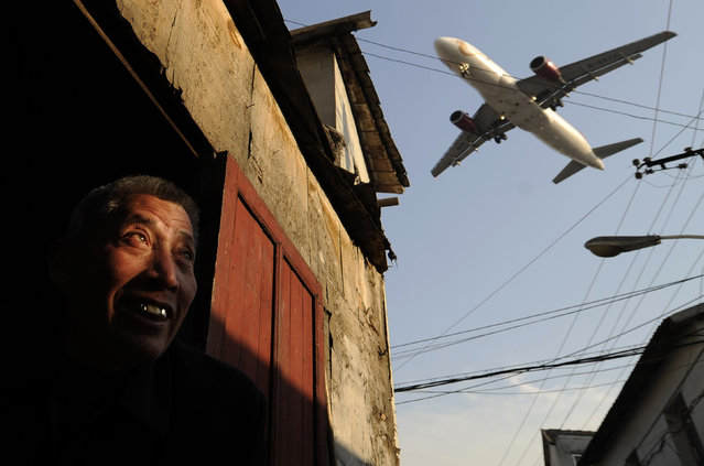 A man watches as an airliner flies over his house into Hongqiao International airport in Shanghai on January 5, 2012. (Photo by Peter Parks/AFP Photo)