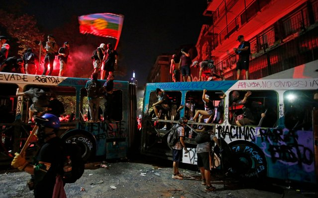 Demonstrators stand on a destroyed a bus during an anti-government protest in Santiago, Chile, Friday, March 13, 2020. Chile has been roiled by continuing street protests since Oct. 18 of last year, when a student protest over a modest increase in subway fares turned into a much larger and broader movement with a long list of demands that largely focus on inequality. (Photo by Luis Hidalgo/AP Photo)