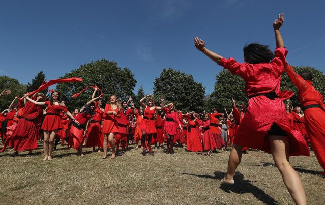 """Both men and women dressed as singer Kate Bush from her 1978 video to her song """"Wuthering Heights"""" dance while seeking to create a new world's record for the most people dancing in costume to the song at once at Tempelhofer Feld park on July 16, 2016 in Berlin, Germany. While a precise account was unavailable just after the event, a calculated estimate put the number of dancers at between 400 and 500, well above the previous record set in 2013 in Brighton, UK of 300. (Photo by Sean Gallup/Getty Images)"""