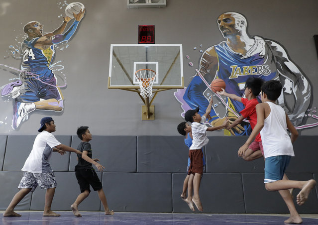 """Boys plays beside images of former NBA basketball player Kobe Bryant at the """"House of Kobe"""" basketball court in Valenzuela, north of Manila, Philippines on Monday, January 27, 2020. Fans left flowers and messages on the walls at the newly inaugurated court after learning of Bryant's death. Bryant died in a helicopter crash. (Photo by Aaron Favila/AP Photo)"""