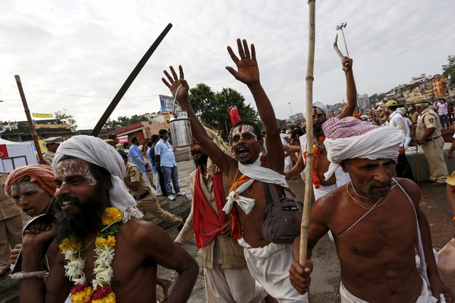Sadhus or Hindu holy men shout religious hymns as they arrive to take a dip in the Godavari river during the first Shahi Snan (grand bath) at Kumbh Mela, or Pitcher Festival in Nashik, India, August 29, 2015. (Photo by Danish Siddiqui/Reuters)