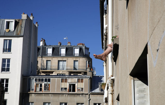 The feet of a woman dangle from a window ledge in the sun during a nationwide confinement to counter the Covid-19 virus, in Paris, Sunday, April 5, 2020. (Photo by Francois Mori/AP Photo)