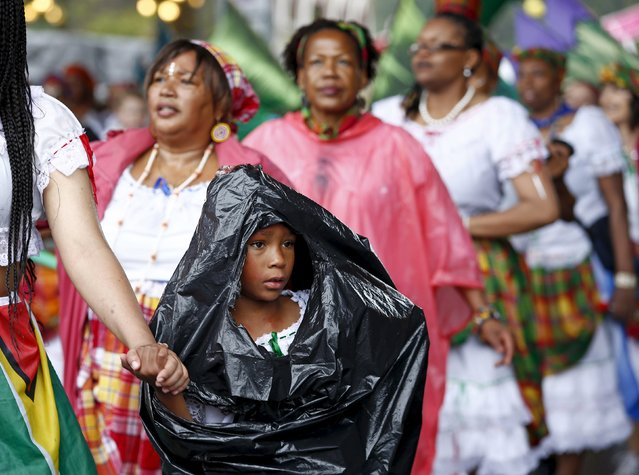 A young performer covers herself from the rain with a plastic bag at the Notting Hill Carnival in west London, August 31, 2015. (Photo by Eddie Keogh/Reuters)