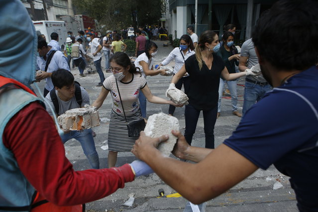 Volunteers pick up the rubble from a building that collapsed during an earthquake in the Condesa neighborhood of Mexico City, Tuesday, September 19, 2017. (Photo by Rebecca Blackwell/AP Photo)