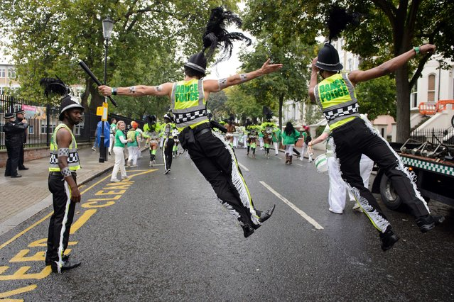 Performers in costumes take part in the parade on the second day of the Notting Hill Carnival in London on August 25, 2014. Heavy rain continued throughout the day, dampening many feathered costumes and performers. The Notting Hill Carnival honours London's Afro-Caribbean culture in an area which was home to thousands of immigrants to Britain from the Caribbean in the 1950s onwards. (Photo by Leon Neal/AFP Photo)