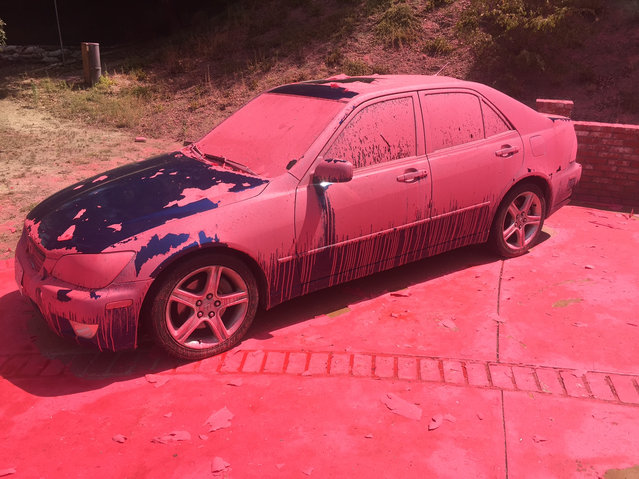 A car covered in aerially-applied fire retardant remains parked in Ruthspring Dr., in Santa Clarita, Calif., on Sunday, July 24, 2016. Two massive wildfires raged in tinder-dry California hills and canyons Sunday, leaving thousands of homes evacuated and authorities to investigate a burned body found in a neighborhood swept by flames. Firefighters have been trying to beat back a fire since Friday that has blackened more than 34 square miles of brush on ridgelines near the city of Santa Clarita and the Angeles National Forest. (Photo by Matt Hartman/AP Photo)