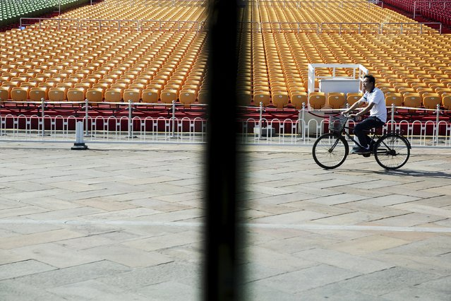 A man cycles past stands raised at Beijing's Tiananmen Square September 2, 2015 as the capital prepares for tomorrow's parade. (Photo by Damir Sagolj/Reuters)