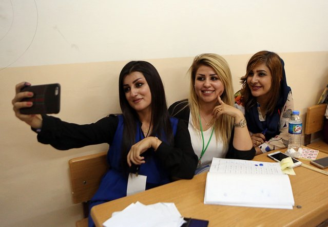 Kurdish Election staff take a picture in a polling station during the referendum on independence from Iraq in Irbil, Iraq, Monday, September 25, 2017. The vote is not binding and is not expected to result in independence any time soon, but was hailed as historic by Kurdish leaders spearheading the campaign. (Photo by Khalid Mohammed/AP Photo)