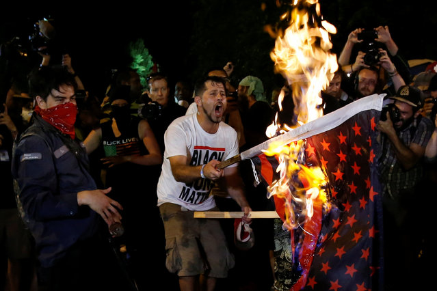 Protesters from various organizations surround men who were burning a modified American flag along the perimeter walls of the 2016 Democratic National Convention in Philadelphia, Pennsylvania on July 27, 2016. (Photo by Adrees Latif/Reuters)