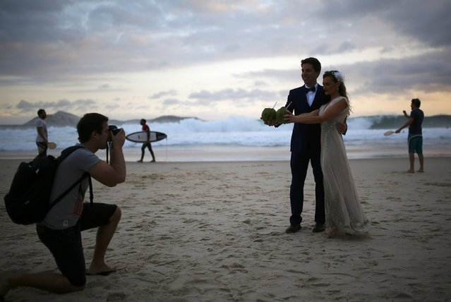 A couple named Elizabeth and Alexandre pose for a photo before their wedding on Arpoador Beach in Rio de Janeiro, Brazil on July 30, 2016. (Photo by Nacho Doce/Reuters)