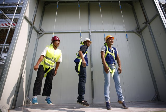Participants hang from ropes as they learn how to use safety gears at an experience centre for construction safety training in Beijing, September 5, 2014. The centre which opened in June 2014 was established to educate workers about construction safety. According to the centre, about 1,000 construction workers undergo 3-hour classes which comprises of 33 modules every month. (Photo by Kim Kyung-Hoon/Reuters)