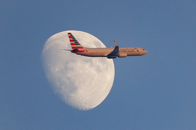 An American Airlines aircraft flies past the moon as the Los Angeles Angels play the Texas Rangers in the first inning of a baseball game, Friday, September 1, 2017, in Arlington, Texas. (Photo by v/AP Photo)