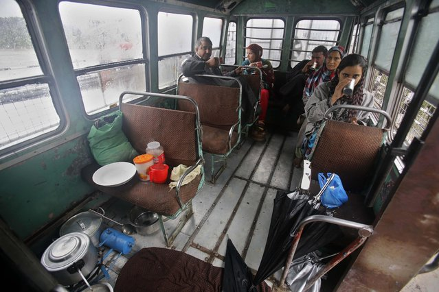 Kashmiris drink tea inside a bus where they have taken shelter after their homes were inundated by floodwaters in Srinagar, India, Saturday, September 6, 2014. (Photo by Mukhtar Khan/AP Photo)