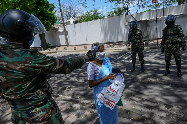 A security personnel (L) checks the body temperature of a pedestrian during a government-imposed nationwide lockdown as a preventive measure against the COVID-19 coronavirus, in Colombo on April 23, 2020. (Photo by Ishara S. Kodikara/AFP Photo)