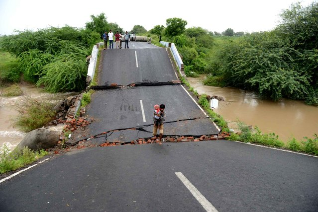An Indian villager holding his baby crosses a collapsed bridge at Tagdi village on Dhaduka – Bhavnagar Highway, some 110 kms from Ahmedabad on September 9, 2014. The India Meterlogical Department (IMD) have warned of heavy rains in Gujarat in coming days. (Photo by Sam Panthaky/AFP Photo)