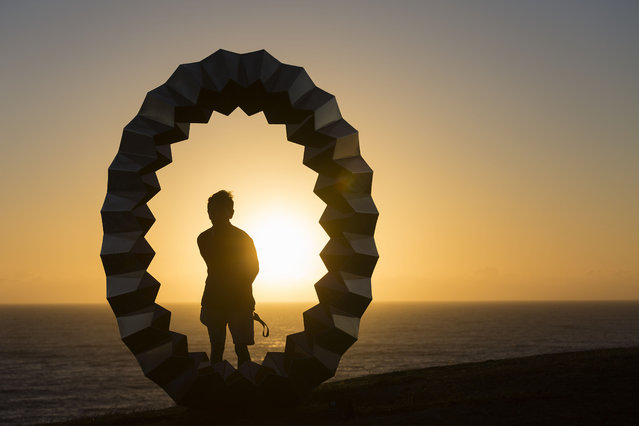 """A man poses for a photo at sunrise by the work entitled """"Foci"""" by Karl Meyer at Sculpture By The Sea at Bondi Beach on October 19, 2017 in Sydney, Australia. """"The artwork is indicative of natural processes; a reflection of form and sequencing throughout nature that directly connects to scale within the natural world. It seeks to evoke a sense of life"""". (Photo by Brook Mitchell/Getty Images)"""