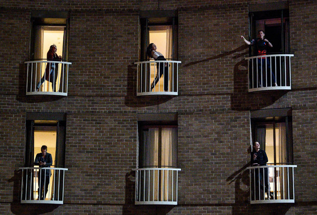 Hotel guests in quarantine, a mandatory protocol for travellers returning to Australia to curb the spread of the coronavirus disease (COVID-19), watch a musical performance from their rooms in Sydney, Australia, May 18, 2020. Picture taken May 18, 2020. (Photo by James Gourley/AAP Image via Reuters)
