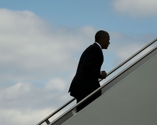 President Barack Obama is seen silhouetted as he walks up the stairs to board Air Force One, Tuesday, September 16, 2014, at Andrews Air Force Base, Md. Obama is traveling to the Centers for Disease Control and Prevention in Atlanta, to address the Ebola crisis and announce a plan to help the West Africa nations fight the spread of the Ebola virus. (Photo by Pablo Martinez Monsivais/AP Photo)
