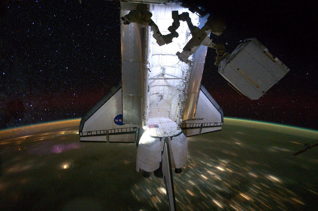 Backdropped by a night time view of the Earth and the starry sky, the Space Shuttle Endeavour is seen docked to the International Space Station on May 28, 2011. (Photo by Reuters/NASA)