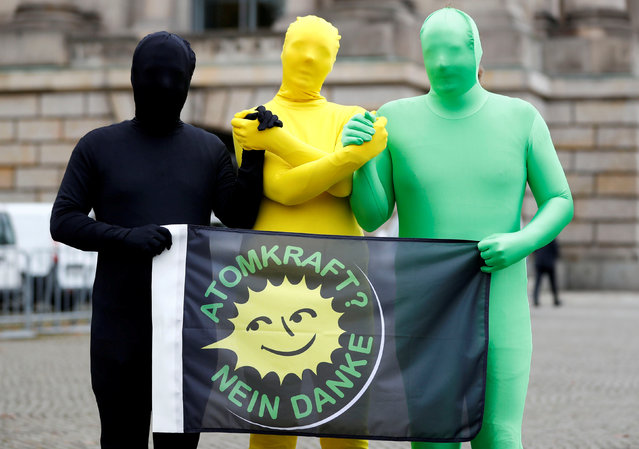 "Environmental activists pose for photographers near the German Parliamentary Society offices during the exploratory talks about forming a new coalition government held by CDU/CSU in Berlin, Germany, October 26, 2017.  The words read ""Nuclear power? No thank you"". (Photo by Fabrizio Bensch/Reuters)"