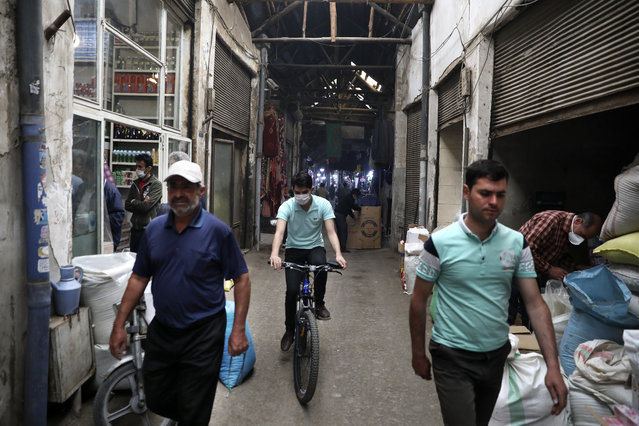 A man rides his bicycle as the others walk through the Qazvin old traditional bazaar some 93 miles (150 kilometers) northwest of the capital Tehran Iran, Wednesday, April 22, 2020. Iran's Revolutionary Guard said it put the Islamic Republic's first military satellite into orbit, dramatically unveiling what experts described as a secret space program with a surprise launch Wednesday that came amid wider tensions with the United States. (Photo by Vahid Salemi/AP Photo)