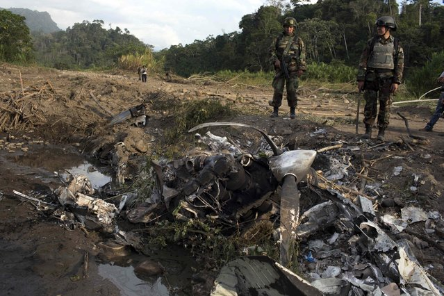 In this Friday, September 19, 2014 photo, Peruvian counternarcotics officers stand next to a plane destroyed allegedly by residents in an effort to hide evidence connected to clandestine airstrip, in the Valley of the Apurimac, Ene and Mantaro River Valleys, or VRAEM, the world's No. 1 coca-growing region in Junin, Peru. Authorities say an average of about 4-5 small planes daily fly into Peru from Bolivia, picking up about 300 kilos each of coca paste in Bolivia, where it is further refined. (Photo by Rodrigo Abd/AP Photo)
