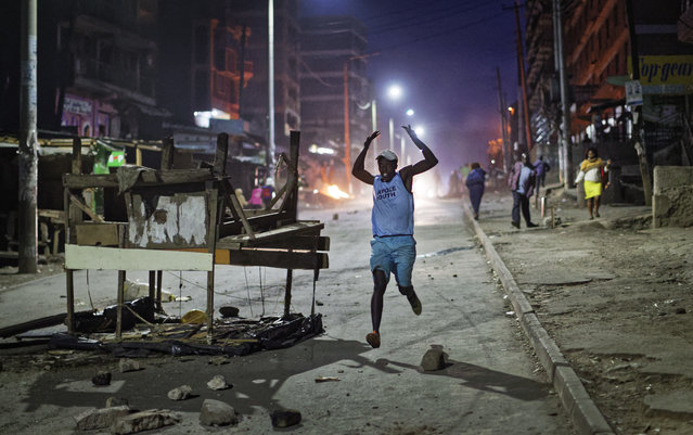A man holds his hands in the air as he runs past a barricade towards riot police during clashes between opposition protesters and police after the election result was announced, in the Mathare area of Nairobi, Kenya, Monday, October 30, 2017. (Photo by Ben Curtis/AP Photo)