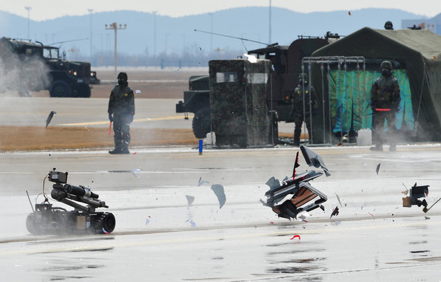 An armed robot controlled by South Korean commandos destroys a mockup of a bomb during an anti-terror drill at Incheon International Airport, west of Seoul, on February 29, 2012. (Photo by Kim Jae-Hwan/AFP Photo)
