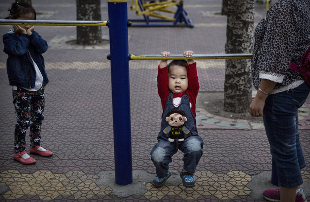 A young Chinese boy hangs from bars while exercising with his mother at a park on September 17, 2014 in Beijing, China. (Photo by Kevin Frayer/Getty Images)