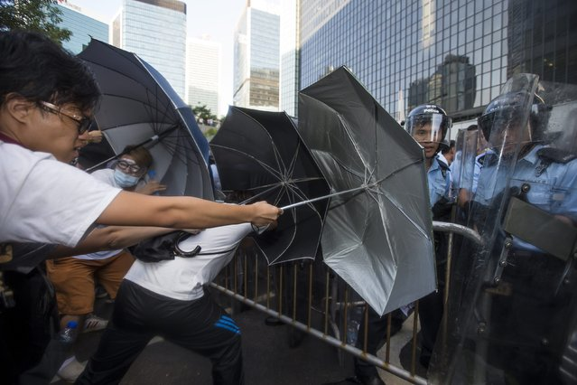 "Riot police scuffle with pro-democracy students after hundreds of protesters stormed into a restricted area at the government headquarters, after a rally ahead of the October 1 ""Occupy Central"" civil disobedience movement in Hong Kong September 27, 2014. (Photo by Tyrone Siu/Reuters)"