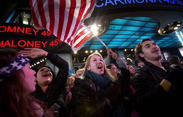 People in New York's Times Square celebrate the news that U.S. President Barack Obama won re-election on November 7, 2012. (Photo by Scott Eells/Bloomberg)