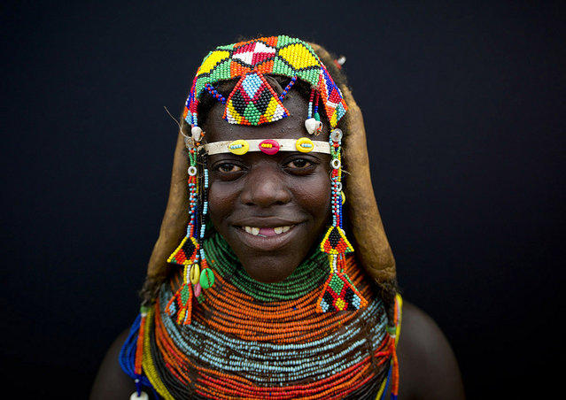 """Happiness of a young wife – Mumuhuila Angola. She smiles as she is happy: she is newly married, and wears her brand new beads necklace. She also shows you her Mumuhuila smile, with teeth removed or cut"". (Eric Lafforgue)"