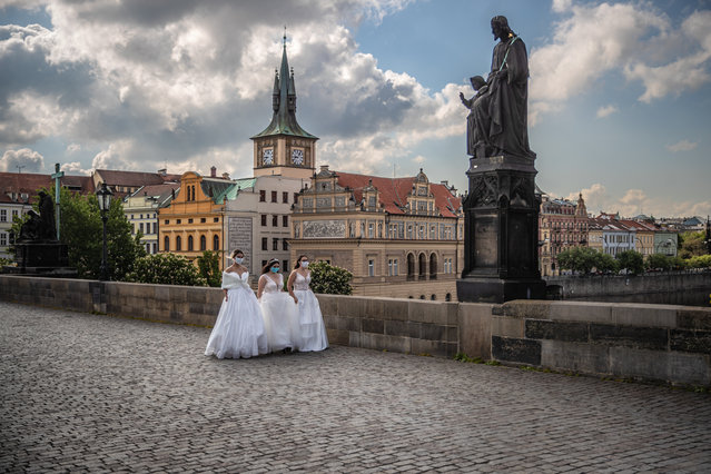 Models, wearing protective face masks and wedding dresses,  walk on the Charles Bridge as they take part in a commercial shot in Prague, Czech Republic, 05 May 2020. Czech government decided to ease the restrictive measures declared to quell the spread of the pandemic COVID-19 disease caused by the SARS-CoV-2 coronavirus. (Photo by Martin Divisek/EPA/EFE)