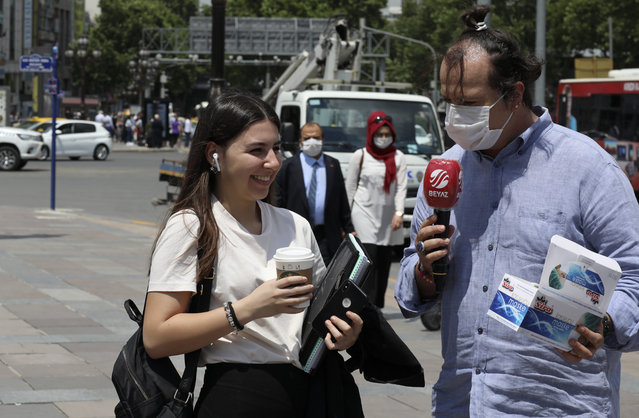 Gencay Unal, a reporter working for Turkey's Beyaz Television channel, wearing face masks to protect against the spread of coronavirus, speaks with a maskless woman in the main Kizilay Square, in Ankara, Turkey, Tuesday, June 16, 2020. Turkey has made the wearing of face masks mandatory in five more provinces, following an uptick in COVID-19 cases. Health Minister Fahrettin Koca tweeted early Tuesday that the wearing of masks is now compulsory in 42 of Turkey's 81 provinces. (Photo by Burhan Ozbilici/AP Photo)
