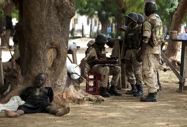 In this Saturday August 1, 2009 file photo, a suspected Islamist extremist member captured by Nigerian troops lies next to a tree in Maiduguri, Nigeria. A Nigerian court has convicted 45 Boko Haram members in the largest mass trial in the Islamic extremist group's history. The closed-door proceedings have raised the concerns of human rights groups about whether the trials of more than 1,600 people will be fair. (Photo by Sunday Alamba/AP Photo)